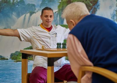 Unterhaltsame Gesellschaftspiel-Runde mit einem Bewohner und Pfleger Vladimir